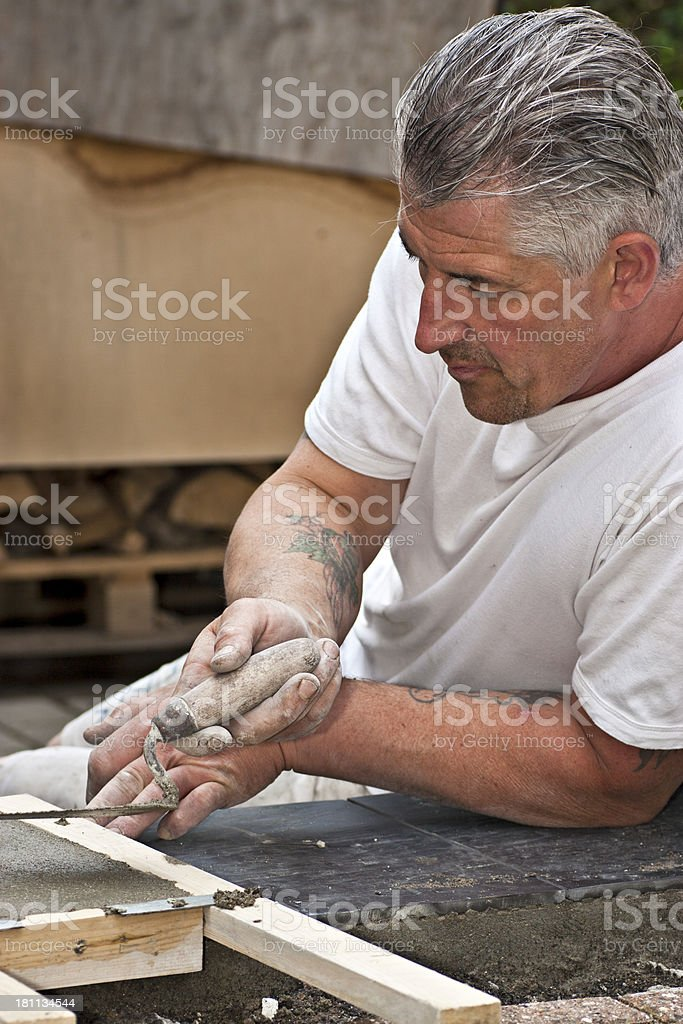 Bricklayer working to polish a staircase with mortar and trowel royalty-free stock photo