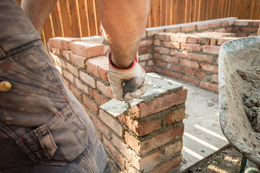 Man is bricklaying outside, building an oven