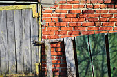 Fragment of a red brick wall and a grey weathered door with a green wooden board
