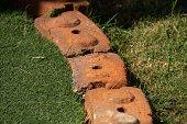 Bricks between artificial grass and the grass in the garden.