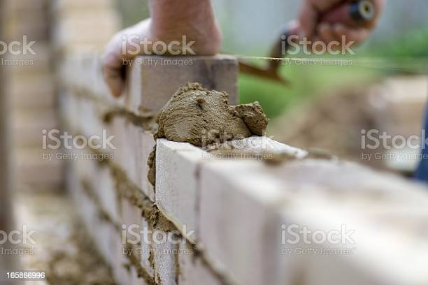 The experienced hands of a bricklayer as he lays the next course of bricks...