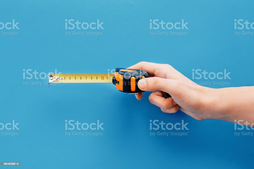 Bricolage concept.Hand holding tape measure on blue background royalty-free stock photo
