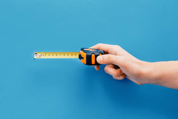 bricolage concept.hand holding tape measure on blue background - measuring stock photos and pictures