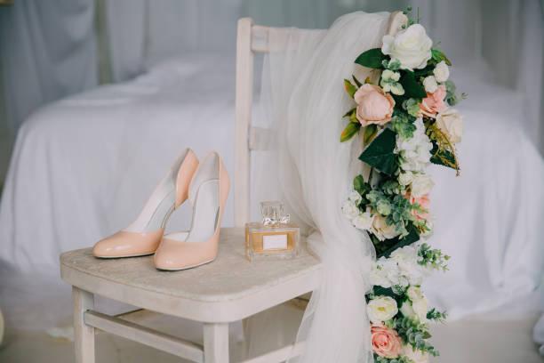 braut-accessoires auf einen weißen stuhl mit blumen, parfüm, schuhe. bekleidungskonzept - brautstyling stock-fotos und bilder