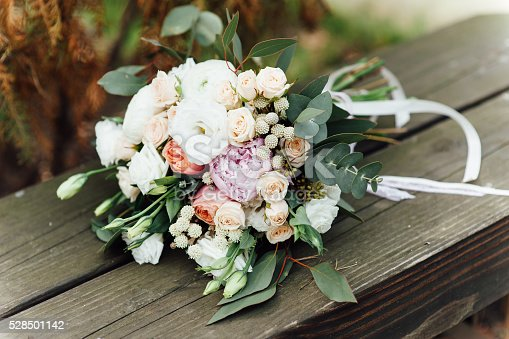 istock Bridal bouquet of roses on a  wooden planks 528501142