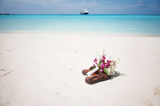 Bridal bouquet on flip flops at the beach and cruise ship at the far end.