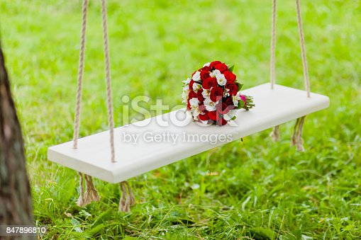 Bridal Bouquet Red and White Roses lying on a rope swing