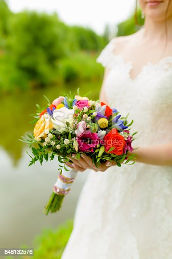 Bride holding bouquet red and white roses in her hands