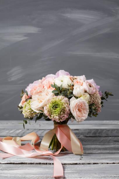 brautstrauß. hochzeit. schöner blumenstrauß von weiß, rosa, blumen und grün, dekoriert mit lange seidenband. auf einem grauen hintergrund. coppy raum - brautstrauß aus holz stock-fotos und bilder