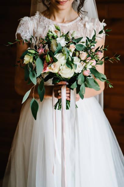 gelin buketi. düğün. kahverengi bir arka planda ayakta beyaz bir elbise içinde kız ve uzun ipek kurdele ile süslenmiş beyaz, sarı, pembe çiçekler ve yeşillikler, güzel bir buket tutar. - beyaz elbise stok fotoğraflar ve resimler
