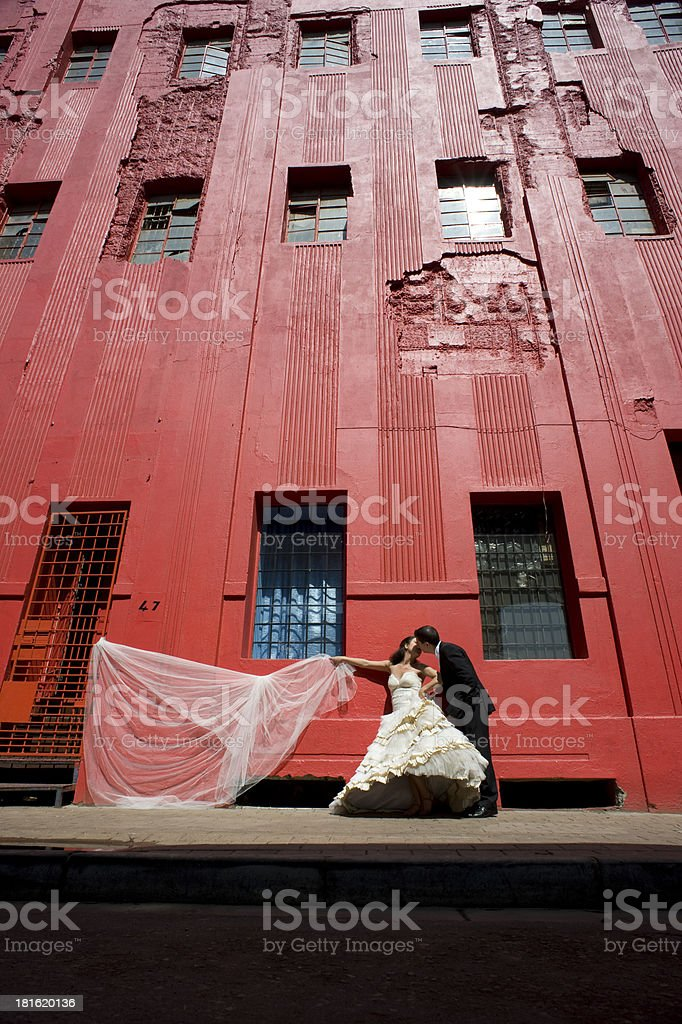 Bridal couple in urbanscape against red painted old building royalty-free stock photo