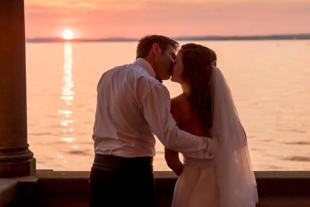 brautpaar küssen am balkon von der alten villa - hochzeitskleid in schwarz stock-fotos und bilder