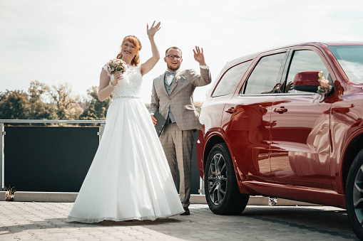 Bridal couple waving on their wedding day