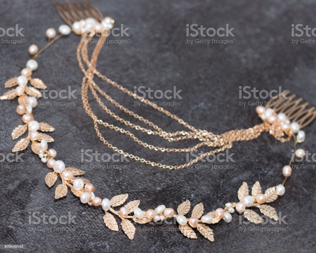 Bridal golden hair wreath with leaves and pearls on gray backgroung....