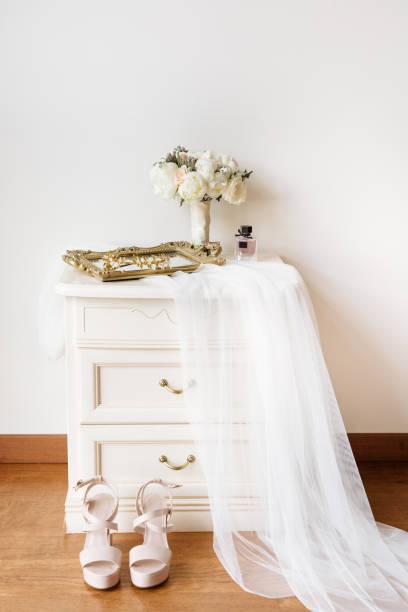 bridal morgen innere zusammensetzung mit weißen schleier, hochzeitsstrauß, rosa schuhe und dem nachttisch. - goldhochzeitsschuhe stock-fotos und bilder