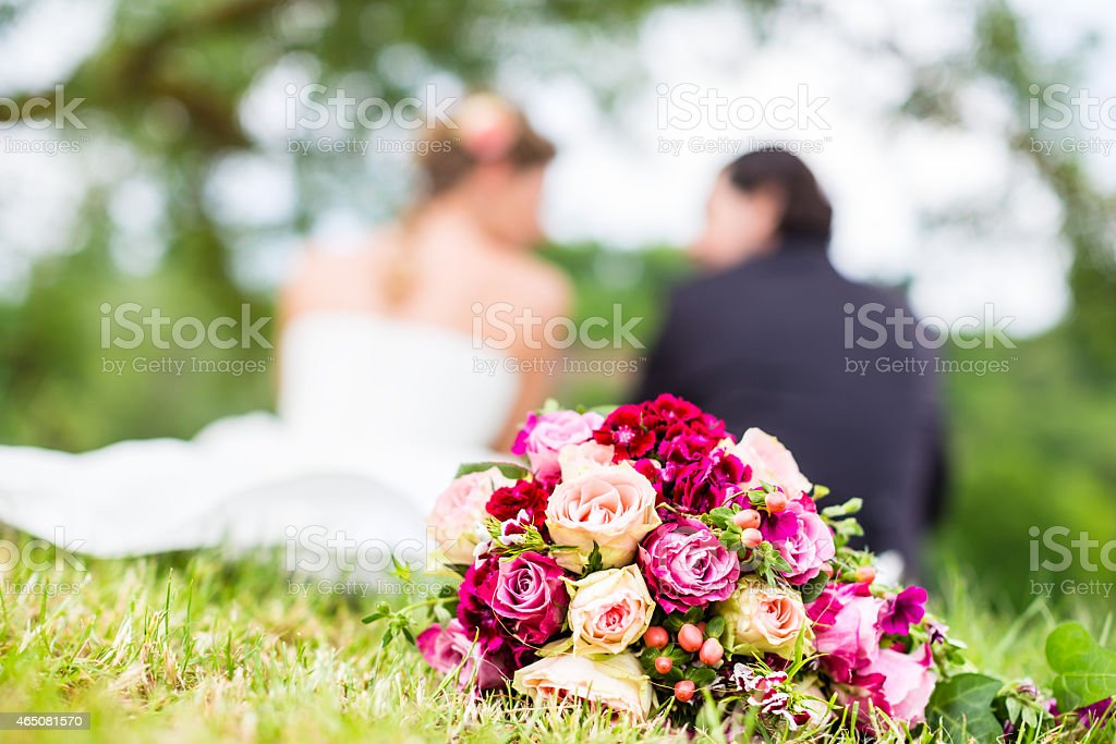 Bridal pair with bouquet sitting on meadow stock photo