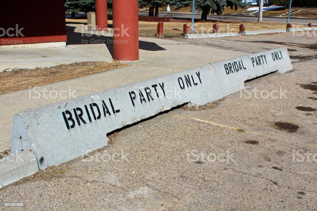 Bridal party only concrete jersey barriers in front of a hall stock photo