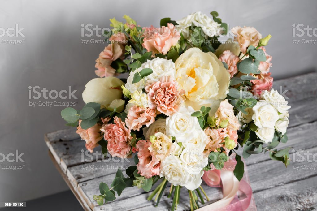 Bridal vintage bouquet. The bride's . Beautiful of mixed flowers and greenery, decorated with silk ribbon, lies on vintage wooden table. vintage style