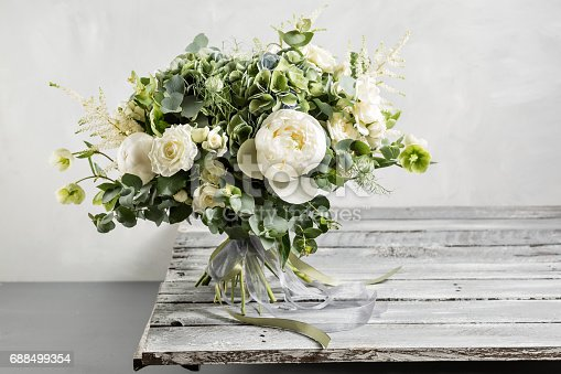 Bridal vintage bouquet. The bride's . Beautiful of mixed flowers and greenery, decorated with silk ribbon, lies on vintage wooden table. vintage style.