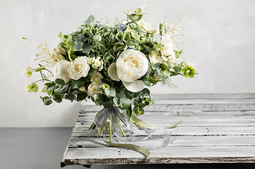 istock Bridal vintage bouquet. The bride's . Beautiful of mixed flowers and greenery, decorated with silk ribbon, lies on vintage wooden table. vintage style 688499354