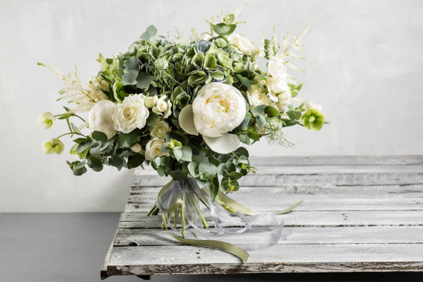 Bridal vintage bouquet. The bride's . Beautiful of mixed flowers and greenery, decorated with silk ribbon, lies on vintage wooden table. vintage style – zdjęcie