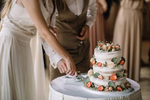 en brud och en brudgum skär sin bröllopstårta - nygift bildbanksfoton och bilder