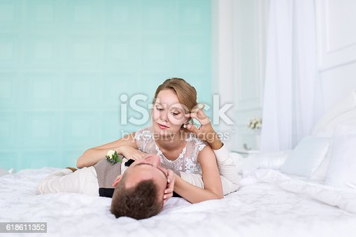 504371332istockphoto Bride and a groom lying on the bed. 618611352