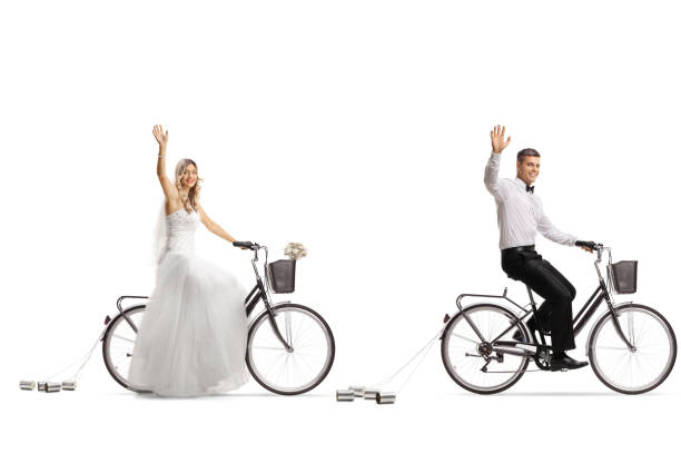 braut und bräutigam reiten fahrräder und winken - zinn hochzeit stock-fotos und bilder