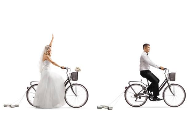 brautpaar auf fahrrädern, die braut winken - zinn hochzeit stock-fotos und bilder