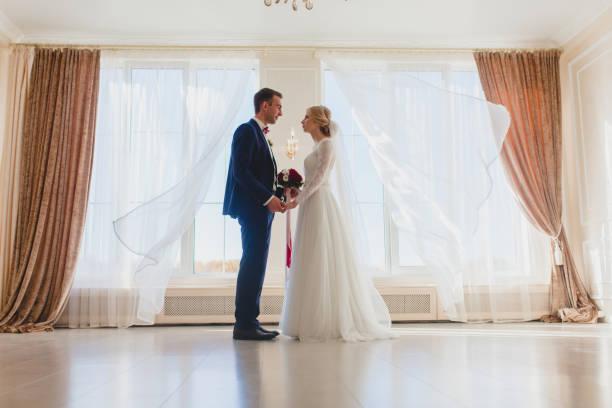Bride and bridegroom standing near the big window stock photo