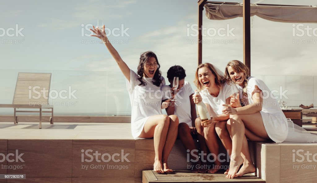 Bride and bridesmaid enjoying rooftop hen party stock photo