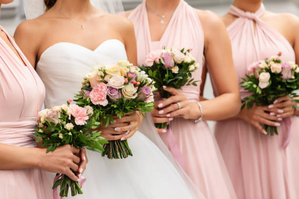Bride and bridesmaids in pink dresses posing with bouquets at wedding day. Happy marriage and wedding party concept stock photo
