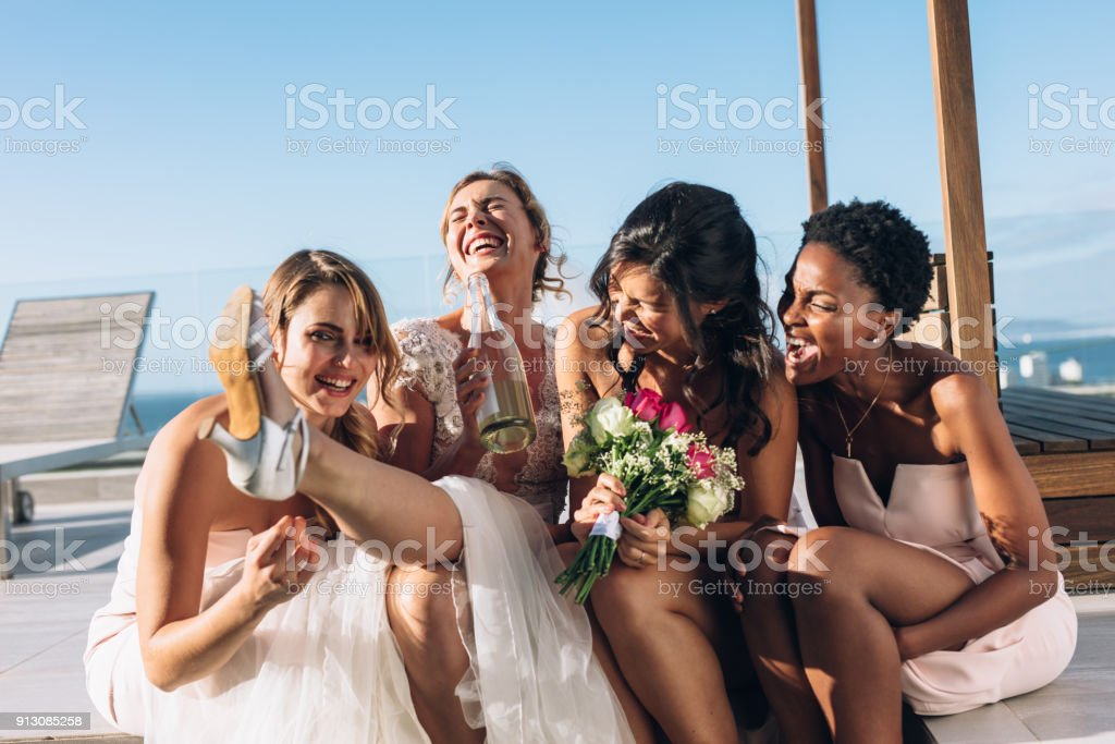 Bride and bridesmaids on rooftop having fun before wedding stock photo