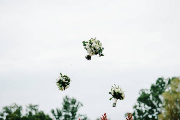 Bride and bridesmaids throwing wedding bouquets in the park on the background of the sky.