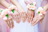 istock Bride and bridesmaids with flower bracelets on hands. Closeup 618964210