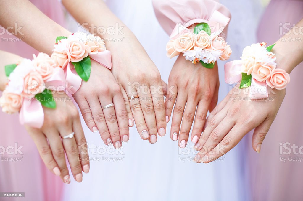 Bride and bridesmaids with flower bracelets on hands. Closeup stock photo