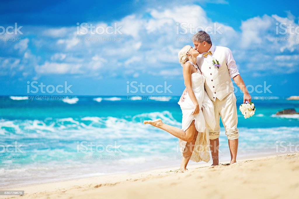 Bride and broom kissing on the beach stock photo