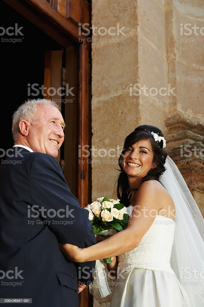 Bride and father entering church, smiling, portrait stock photo