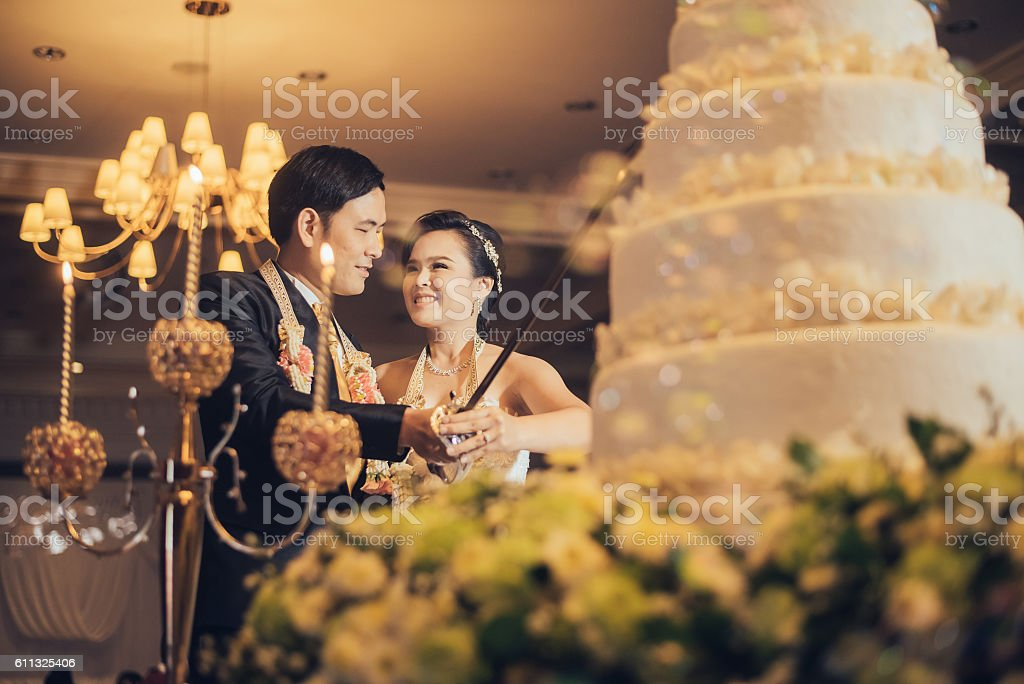 Bride and groom are cutting cake stock photo