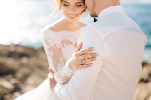 bride and groom are hugging on the rocky beach of the Mamula island. High quality photo