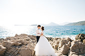 bride and groom are hugging on the rocky beach of the Mamula island against the background of the Arza fortress. High quality photo