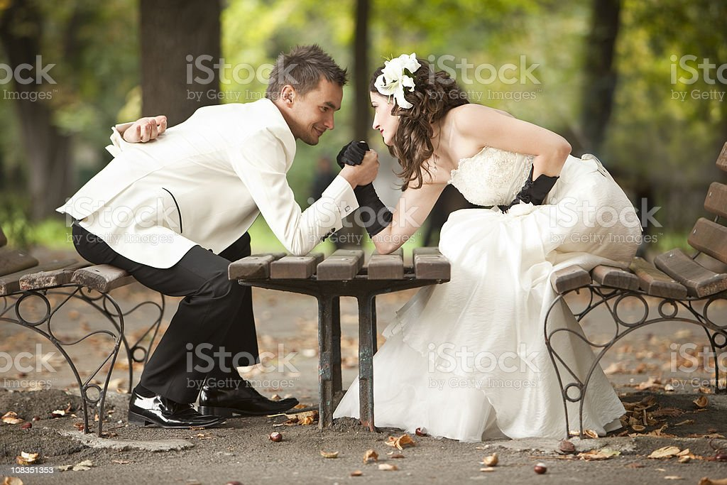 Bride and groom arm wrestling royalty-free stock photo