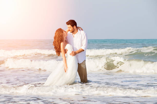 Bride and groom at beach stock photo
