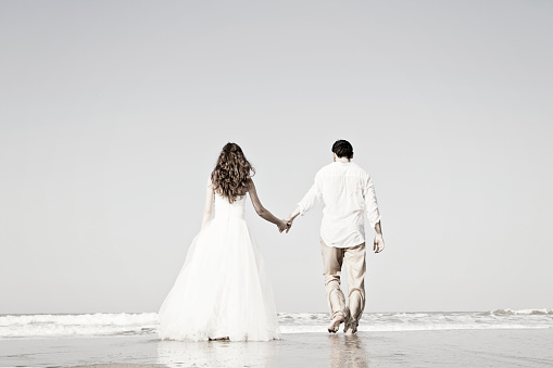 istock Bride and groom at beach 854135126
