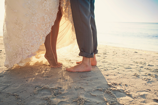 Bride's and groom's feet on the sand at the beach