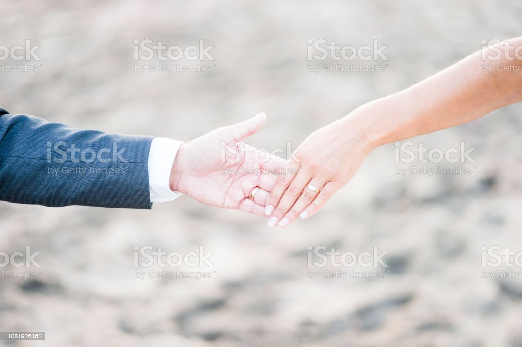 Bride and groom barely holding hands of each other stock photo