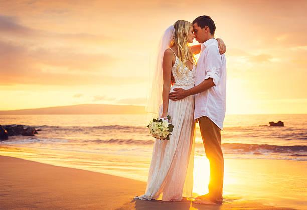 braut und bräutigam an wunderschönen tropischen strand bei sonnenuntergang - verlobungskleider stock-fotos und bilder
