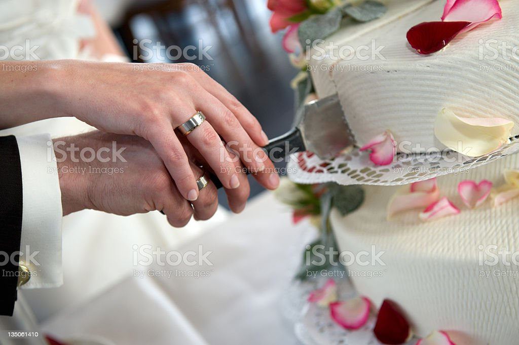 Bride and groom cut their wedding cake together stock photo