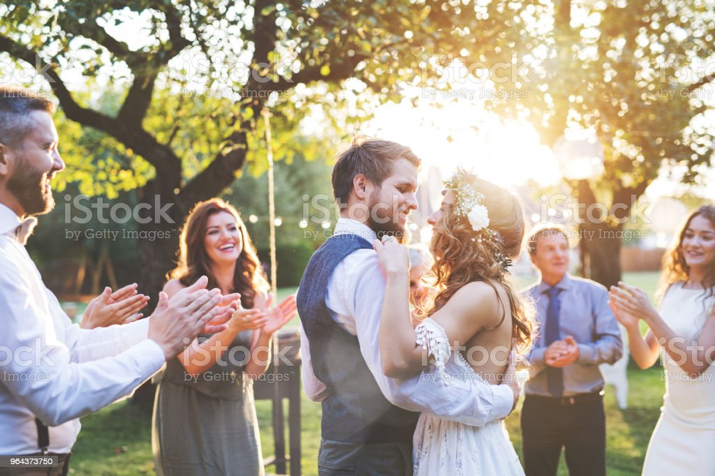 Bride and groom dancing at wedding reception outside in the backyard. stock photo