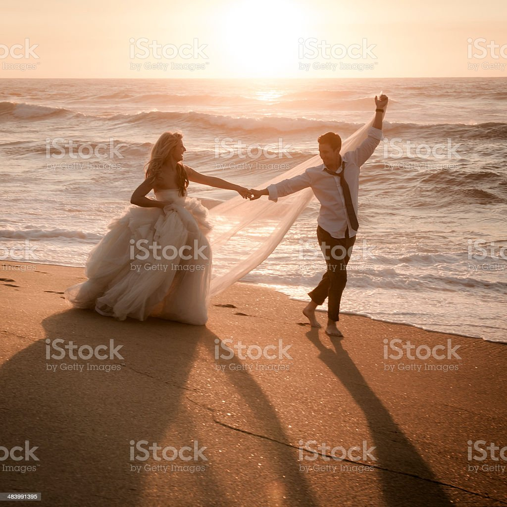 Bride and groom dancing on beach at sunrise stock photo
